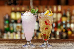 Set cocktails for children. Refreshing cocktails for children on the bar, with apple juice, cranberries, banana syrup, plenty of ice. Space for text Stock Images