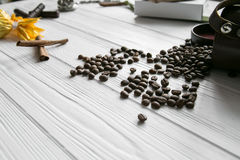 Set of coffee beans and chocolate sweets and packs and pocket watch. White wooden background Royalty Free Stock Photo