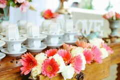 Set of coffee cups and flower arrangement