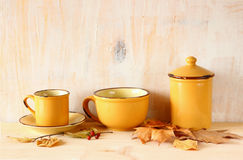 Set of coffee mugs and old jar over wooden rustic table and autumn leaves. filtered image Stock Photos