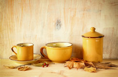 Set of coffee mugs and old jar over wooden rustic table and autumn leaves. filtered image. Royalty Free Stock Photography