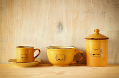 Set of coffee mugs and old jar over wooden rustic table. filtered image. Stock Photos