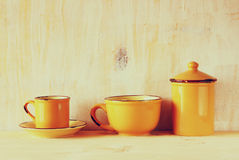 Set of coffee mugs and old jar over wooden rustic table. filtered image. Stock Photo