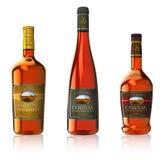 Set of cognac bottles. Set of three cognac bottles isolated on white reflective background Royalty Free Stock Photos