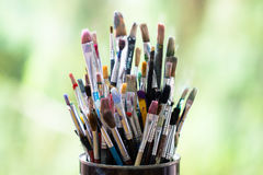 Set of color messy paint brushes in metal tin can on the window Stock Images