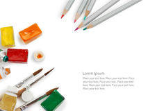 Set of color pencils used watercolor boxes, tubes and paint brushes. Top view. Isolated image with space for your text Stock Images