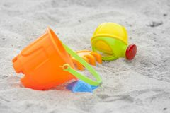 Set of color plastic toys on a sand. An orange bucket and a green sprinkler on the sandbox, including the dolls Stock Photos