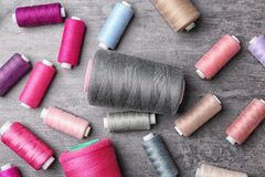 Set of color sewing threads on grey background. Top view Stock Photos