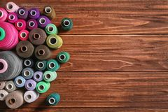 Set of color sewing threads on wooden background Royalty Free Stock Photo