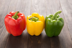 Set of colored bell peppers on wooden background Royalty Free Stock Photography