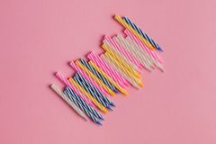 Set of colored birthday candles isolated on pink background. stock images