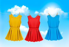 Set of colored dresses hanging on a clothesline on a sunny day. Vector illustration Stock Images