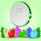 A set of colored Easter eggs with a green tag on a light green background with leaves. Stock Image