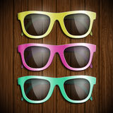Set of colored glasses on a wooden surface. Symbol of glamor and Stock Photography