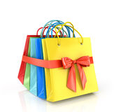 A set of colored paper shopping bags, wrap a red ribbon on a whi Stock Image