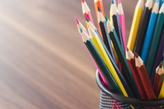 Set of colored pencils in the clerical cup. On the wooden background royalty free stock photography