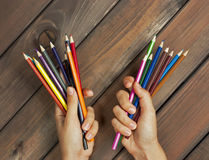 Set of colored pencils in female hands on a background of dark w Royalty Free Stock Photos