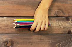 Set of colored pencils in female hands on a background of dark w Stock Photos