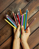 Set of colored pencils in female hands on a background of dark w Royalty Free Stock Photography