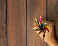Set of colored pencils in female hands on a background of dark w Royalty Free Stock Photo