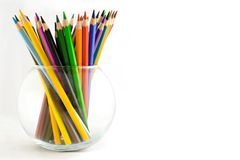 Set of colored pencils in the glass vase. On white background stock image