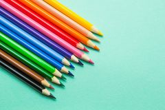 Set of colored pencils on a green background. Preparation for school royalty free stock image