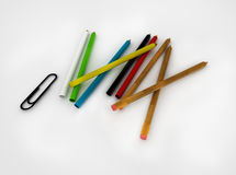 Set of colored pencils and paper clips on a white background royalty free stock images