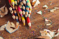 Set of colored pencils with shavings, wooden background Stock Photography