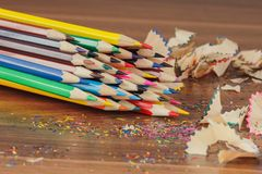 Set of colored pencils with shavings, wooden background Stock Photo