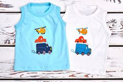Set of colored printed t-shirts for kids. Baby boy new collection of high quality cartoon t-shirts, old wooden bakground, top view royalty free stock photos