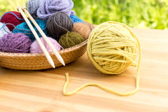 Set of colored yarn balls and needles on straw plate close up Royalty Free Stock Images