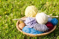Set of colored yarn balls and needles on straw plate Royalty Free Stock Photos