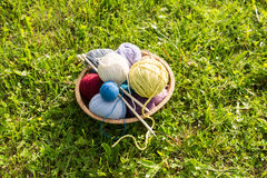 Set of colored yarn balls and needles on straw plate Stock Image