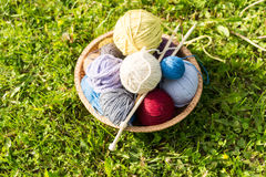 Set of colored yarn balls and needles on straw plate Royalty Free Stock Images