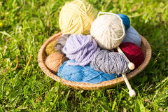 Set of colored yarn balls and needles on straw plate Stock Images