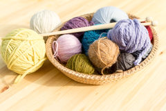 Set of colored yarn balls and needles on straw plate Royalty Free Stock Photo