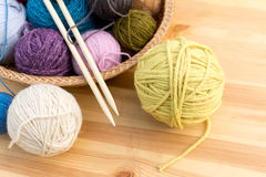 Set of colored yarn balls and needles on straw plate Stock Photography