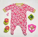 Set of colorful baby clothes. Top view of colorful fashionable baby girl set of clothes with toys and other stuff royalty free stock images