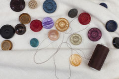 Set of colorful buttons and thread reel. Set of colorful sewing buttons and brown thread reel on white linen fabric Royalty Free Stock Images