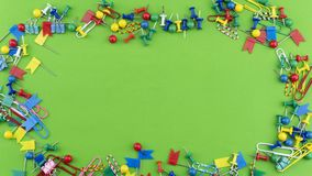 Set of colorful color push pins Thumbtacks frame top view isolated on green background stock photography