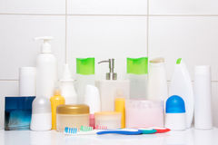 Set of colorful cosmetic bottles over white tiled wall Royalty Free Stock Images