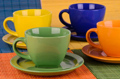 A set of colorful cups with plates Stock Images