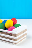 Set of colorful Easter eggs in a white wooden box. On blue backgrounds Royalty Free Stock Images