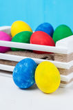 Set of colorful Easter eggs. In a white wooden box on blue backgrounds Stock Photo