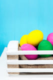 Set of colorful Easter eggs in a white wooden box. On blue backgrounds Stock Photo