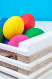 Set of colorful Easter eggs in a white wooden box. On blue backgrounds Royalty Free Stock Photo