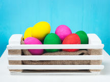 Set of colorful Easter eggs. In a white wooden box on blue backgrounds Royalty Free Stock Photo