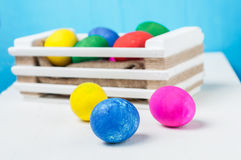 Set of colorful Easter eggs. In a white wooden box on blue backgrounds Royalty Free Stock Images