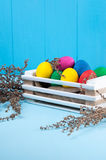Set of colorful Easter eggs in a white wooden box. On blue wooden backgrounds with decorative flowers Royalty Free Stock Photos