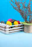 Set of colorful Easter eggs in a white wooden box. On blue wooden backgrounds with decorative flowers Royalty Free Stock Photo